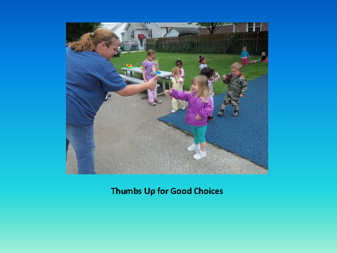Thumbs Up for Good Choices [photograph: teacher with two toddlers]