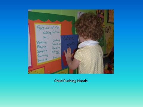 Child Pushing Hands [photograph: toddler in front of wall newspaper]