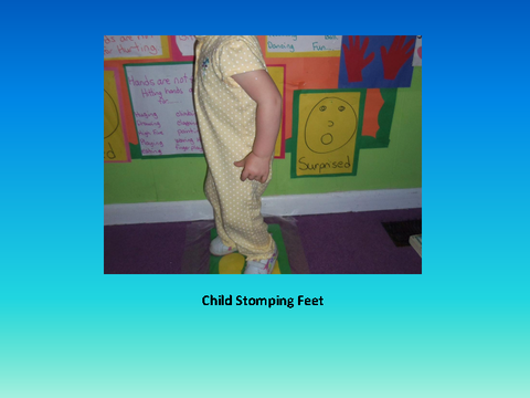 Child Stomping Feet [photograph: toddler in front of wall newspaper]