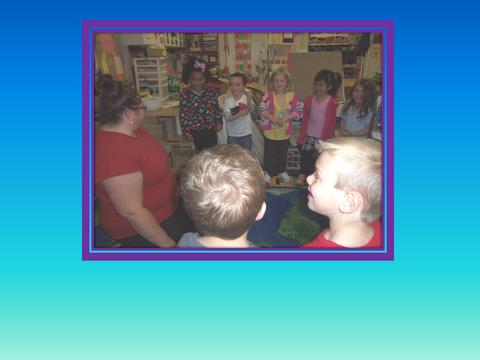 [photograph: children and teacher in class room]