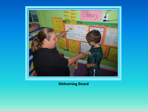 Welcoming Board [photograph: teacher and boy in front of wall newspaper]