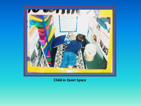 Child in Quiet Space [photograph: child on mat in class room]